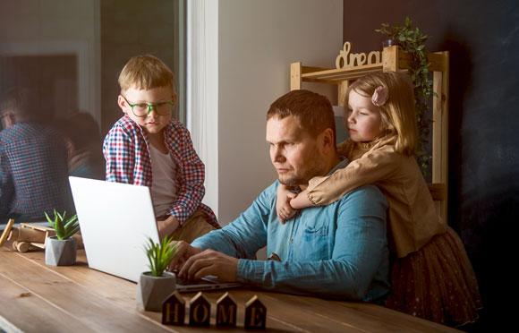 גבר עובד בבית עם ילדים סביבו